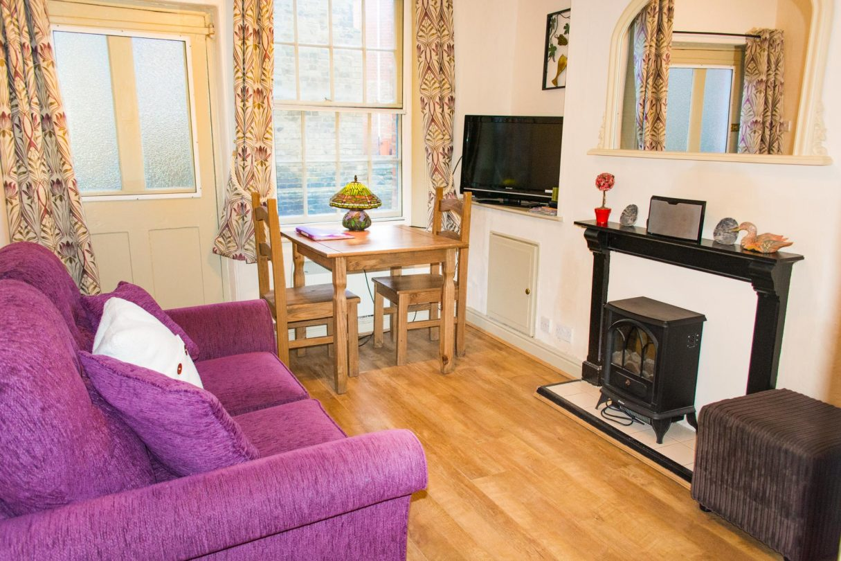 Living area of Fisherman's Cottage, featuring a purple sofa, and dining area.