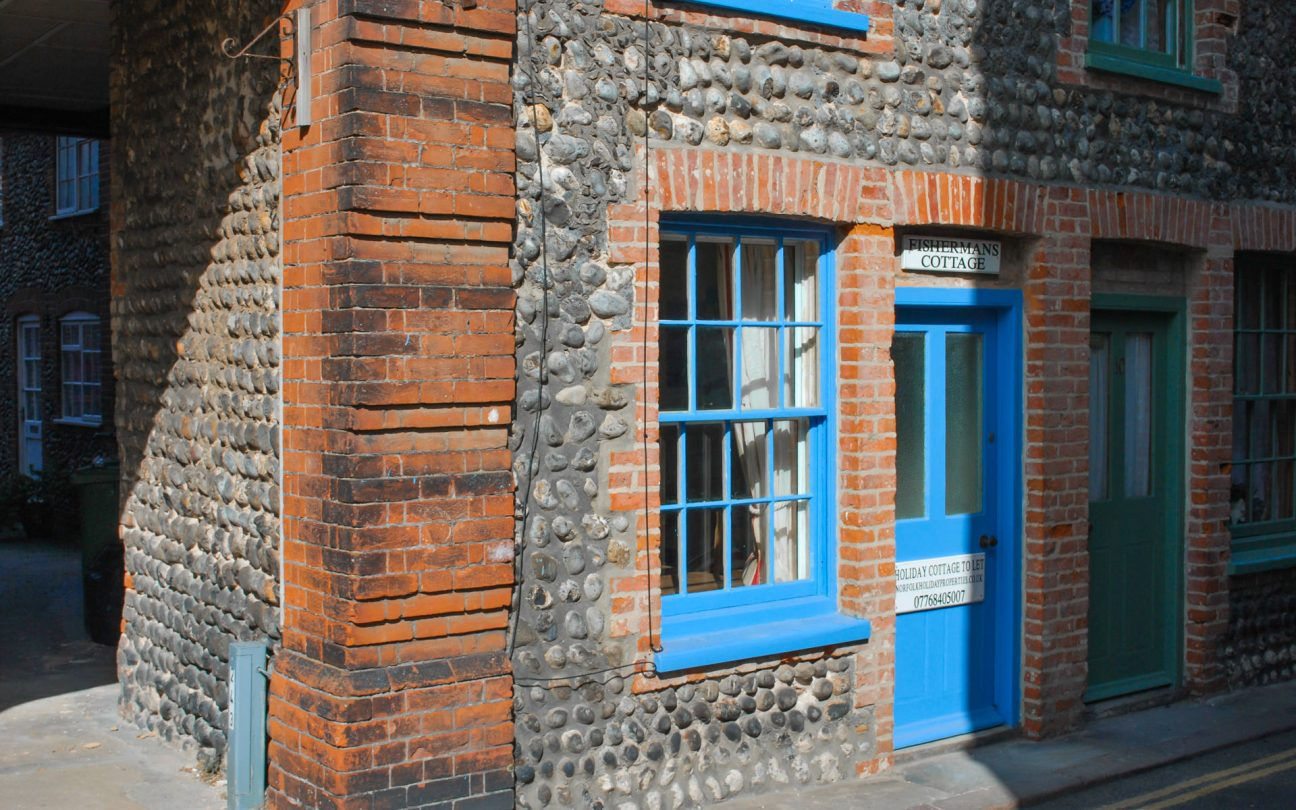Outside shot of Fisherman's Cottage, showing the blue framed windows and door.