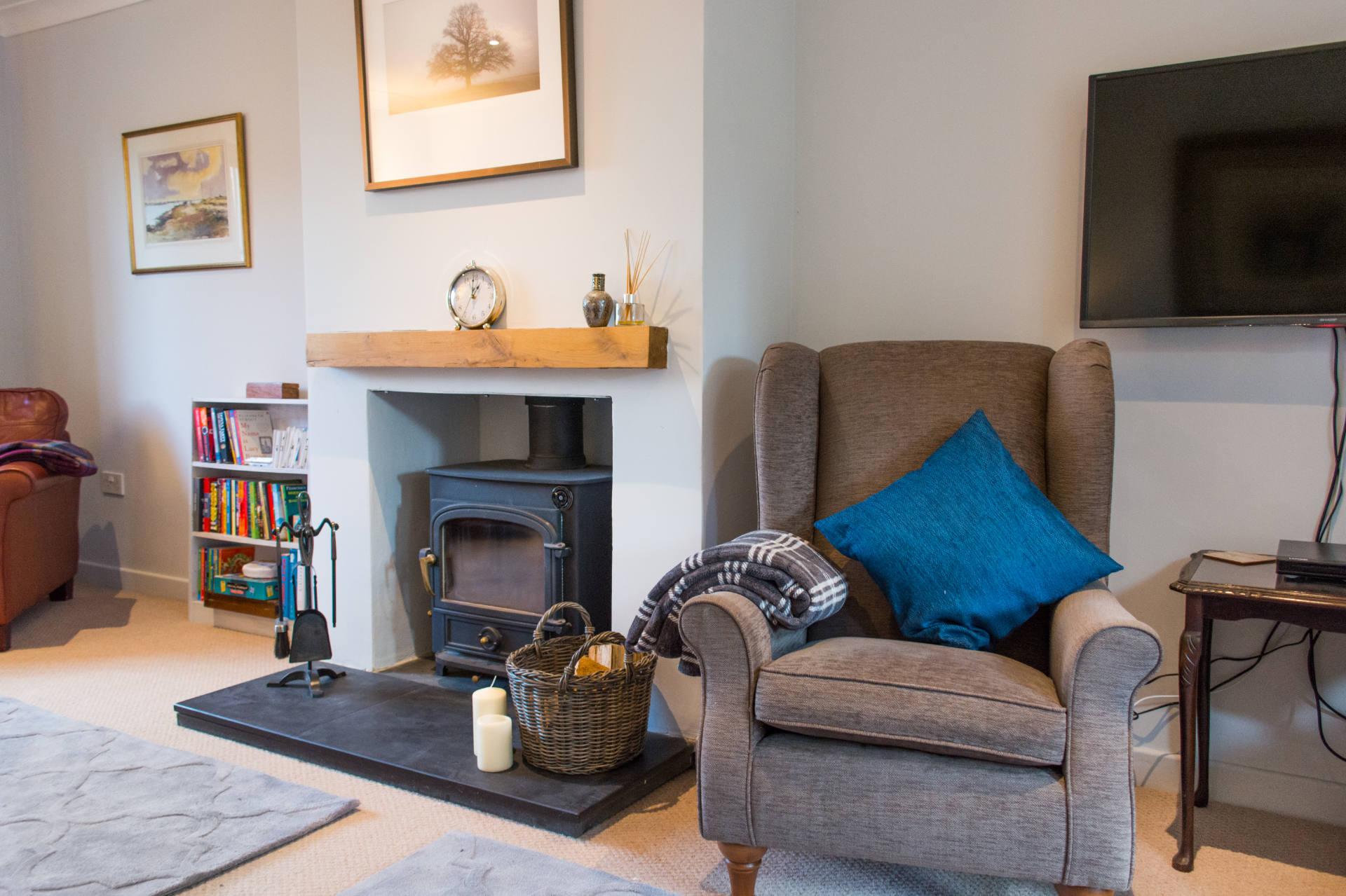 Armchair with a blue pillow next to the log burner fireplace.