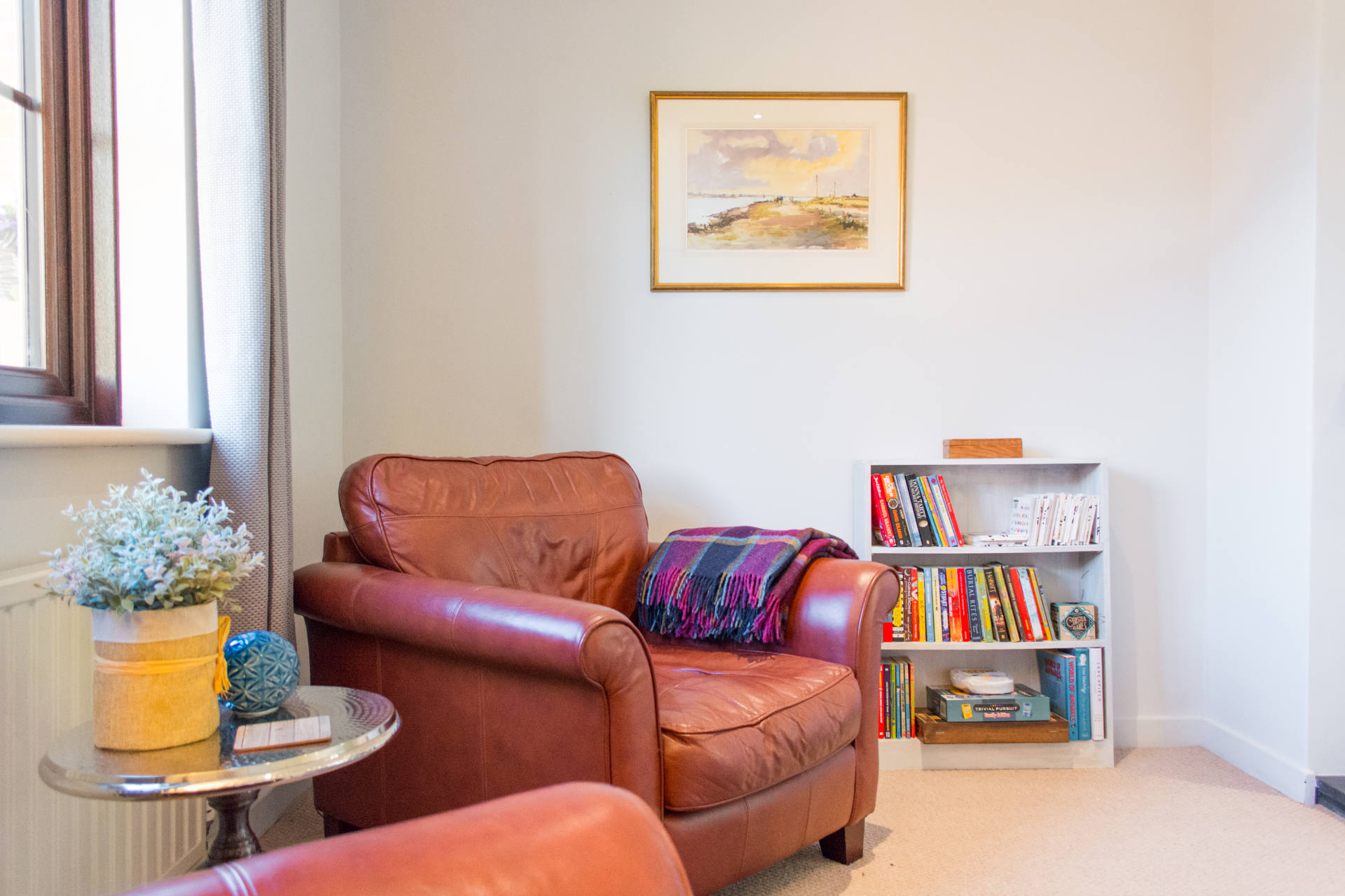 Red leather arm chairs and bookcase.