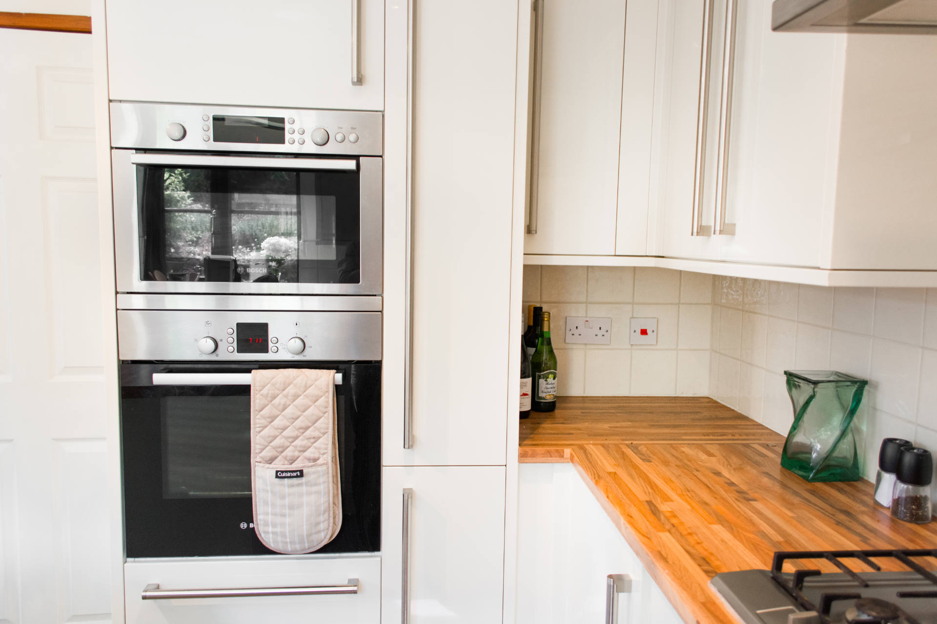 Kitchen worktop and oven with oven gloves.
