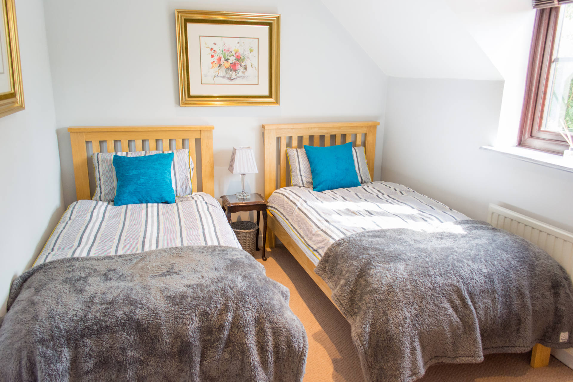 Twin bedroom, with dark grey blankets over the end of the beds and small blue decorative pillows.
