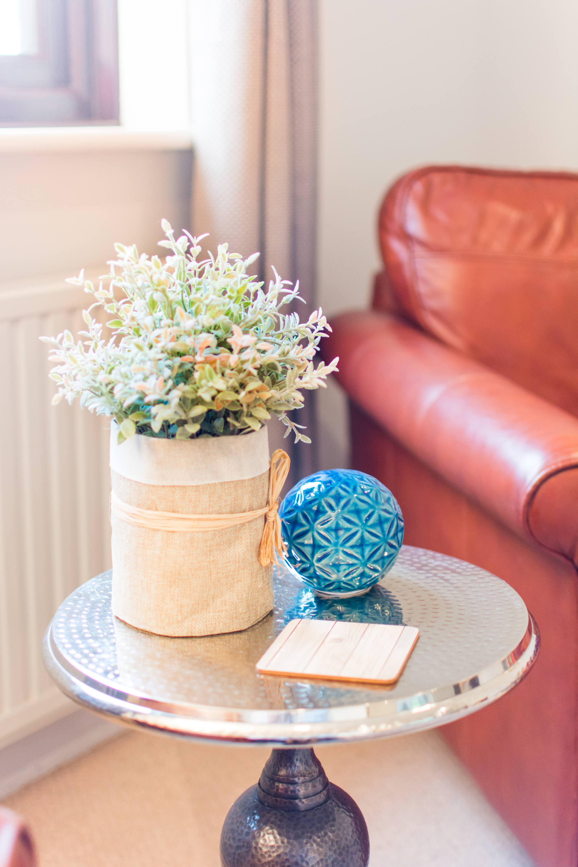 Coffee table and flowers next to red leather arm chair.