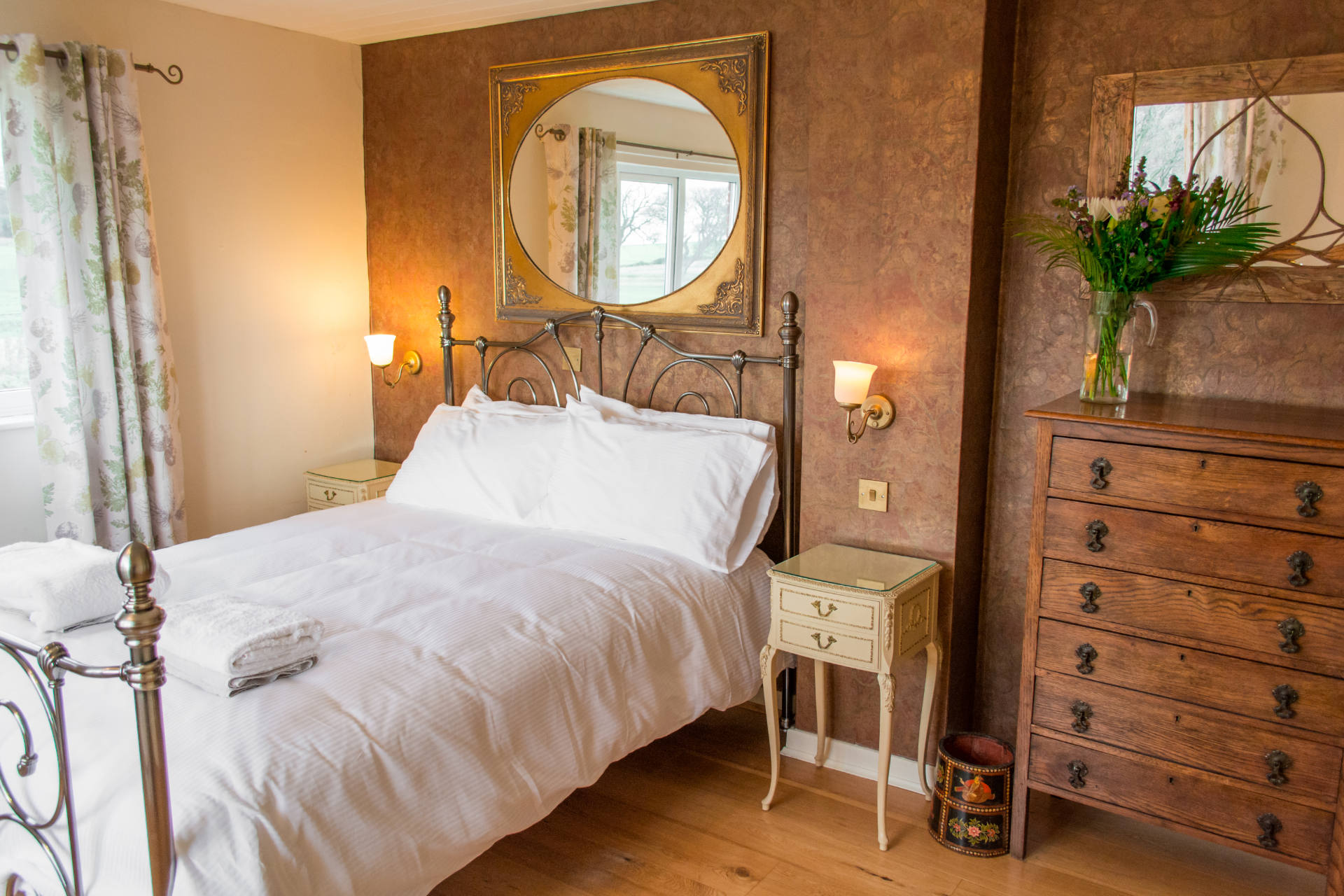 Manor Lodge's master bedroom with mirror over the bed and bedside table.