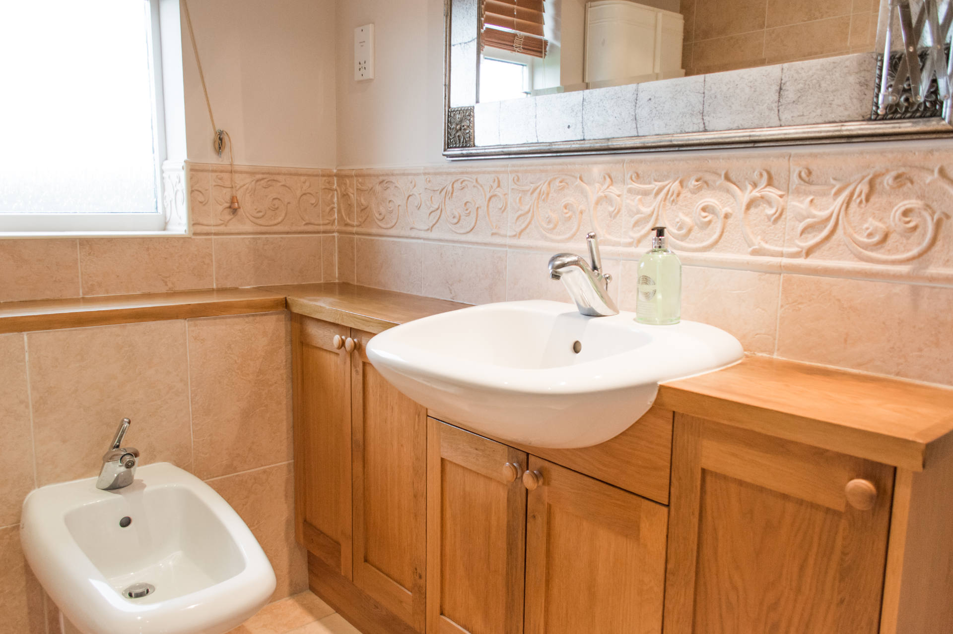 Bathroom sink with wooden cupboards for storage.