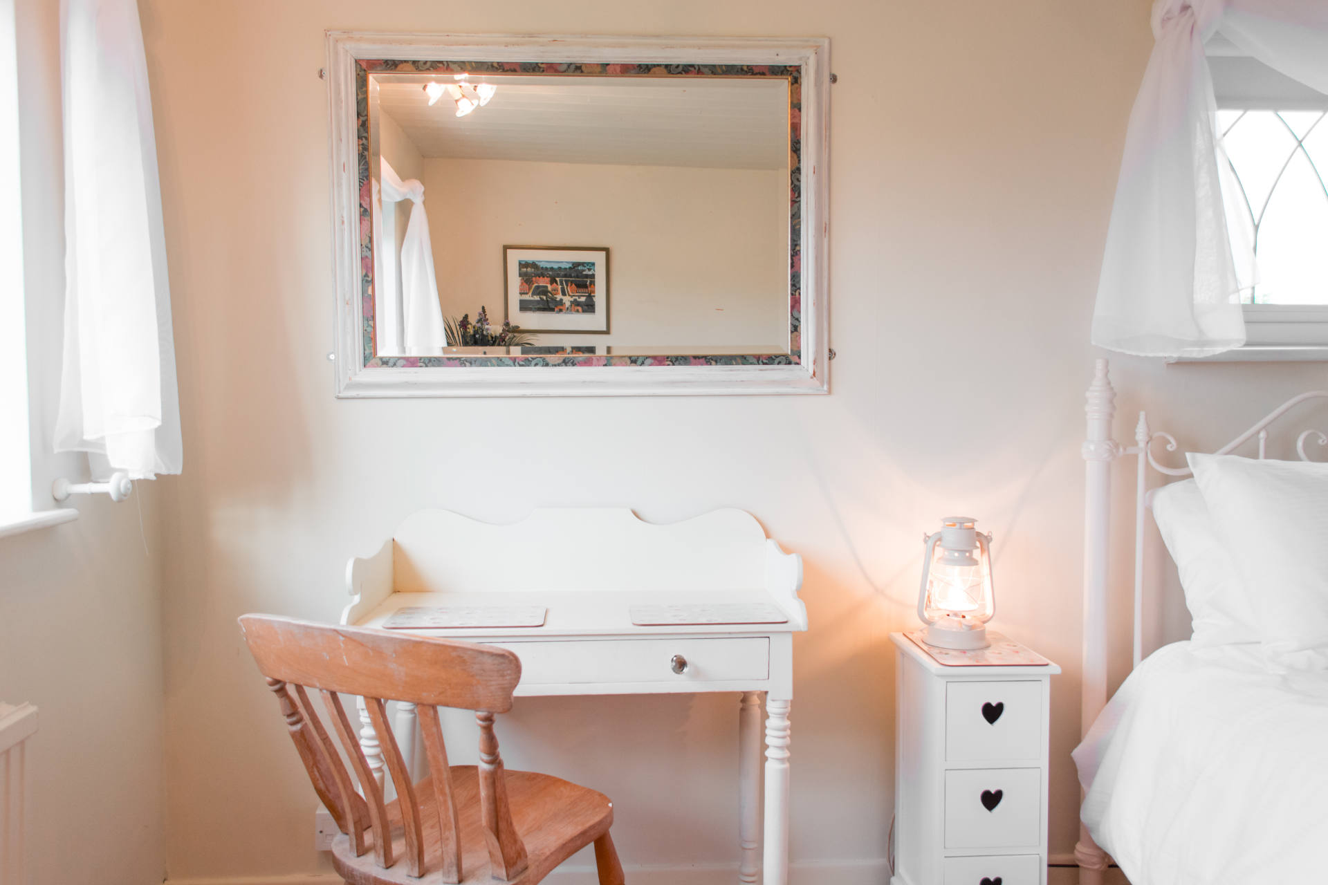 Dresser table, mirror and chair with lamp.