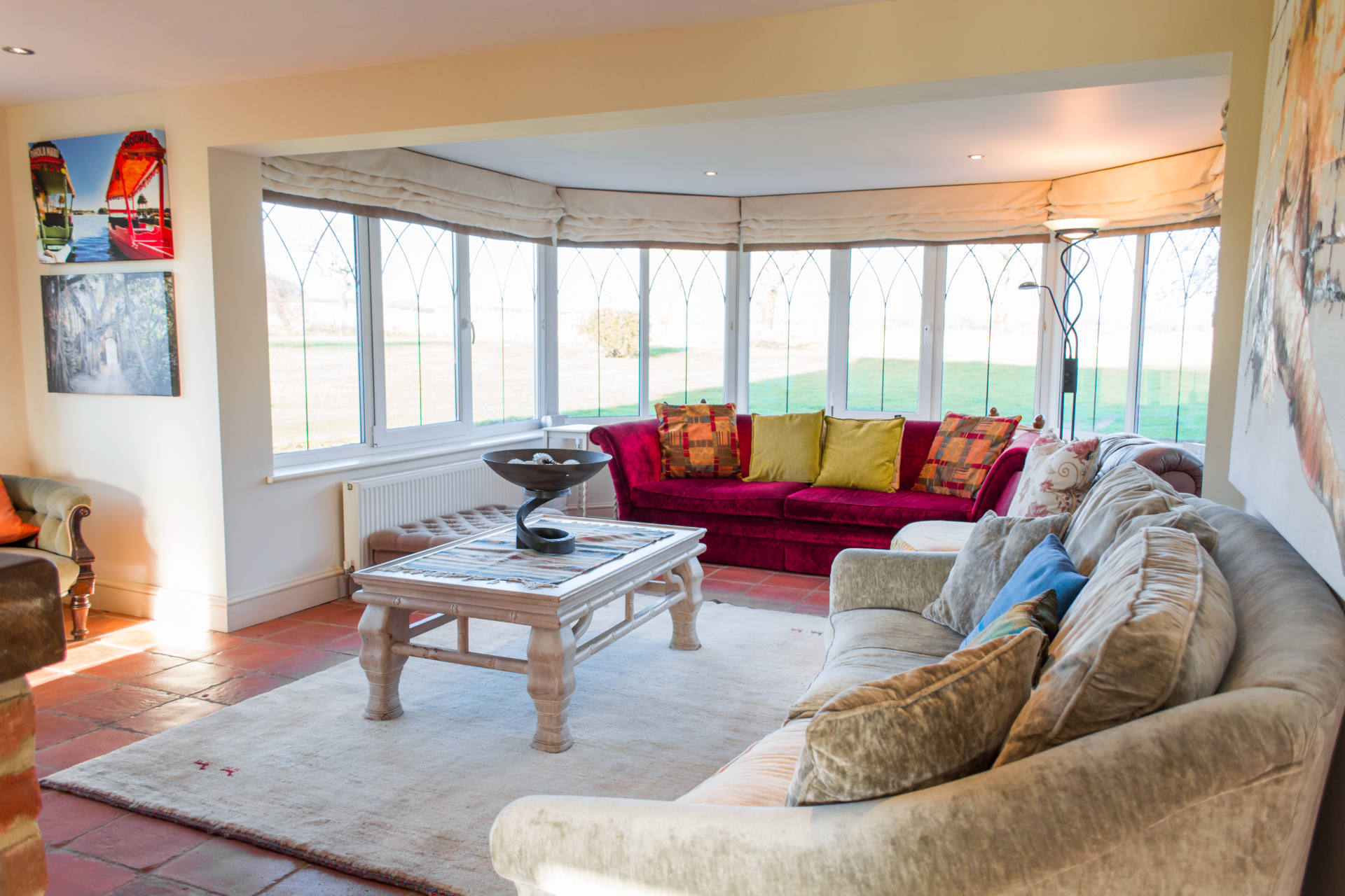 Manor Lodge living room with sofas, coffee table and surrounding large glass windows looking over the garden.