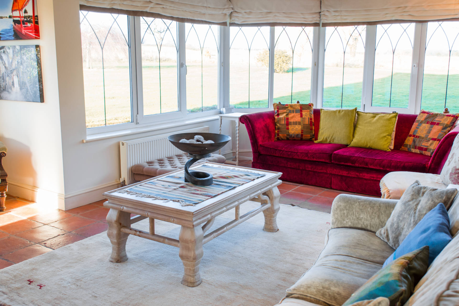 Red sofa and coffee table with surrounding glass windows looking at the garden.