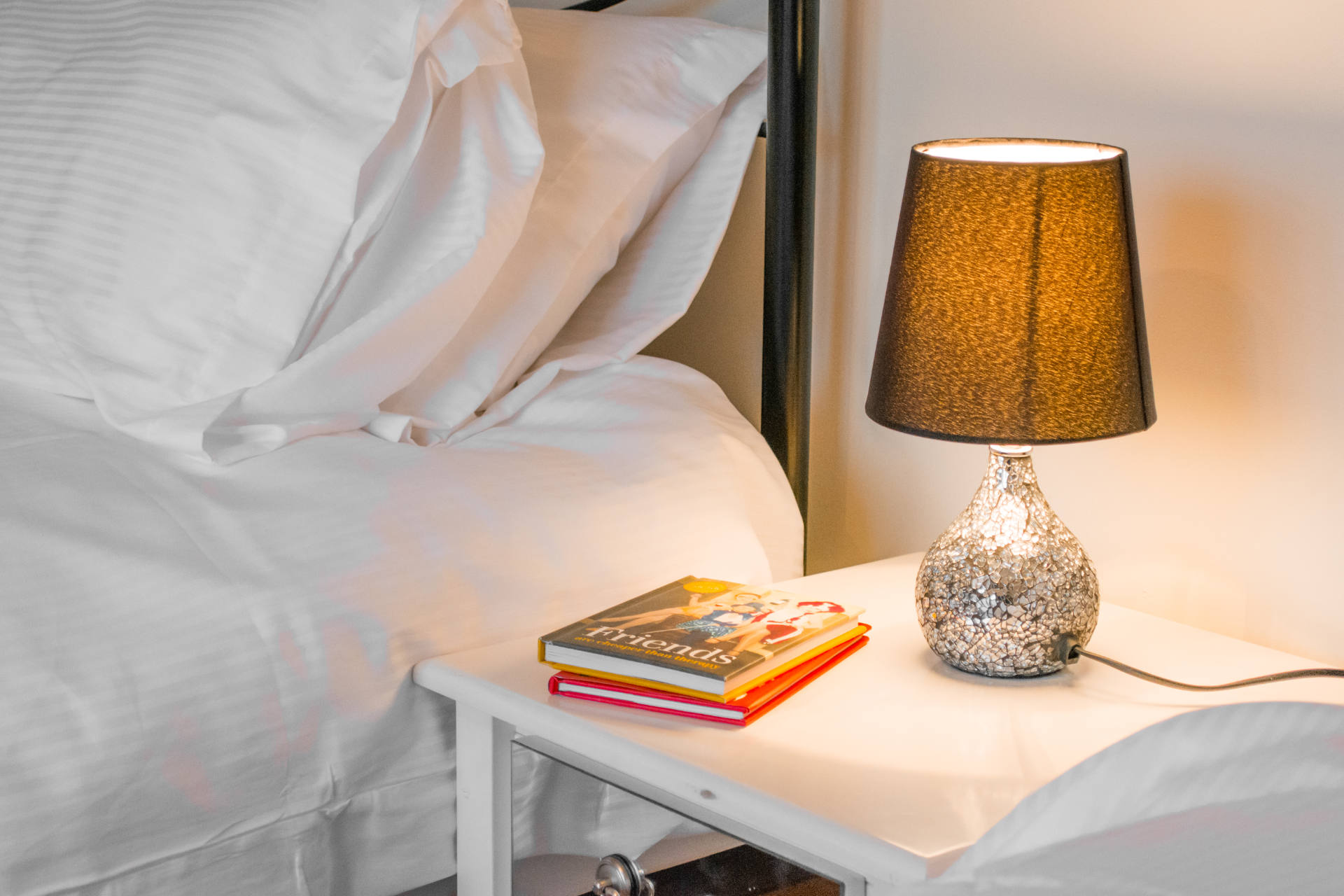 Close up shot of bedside table with book and lamp.