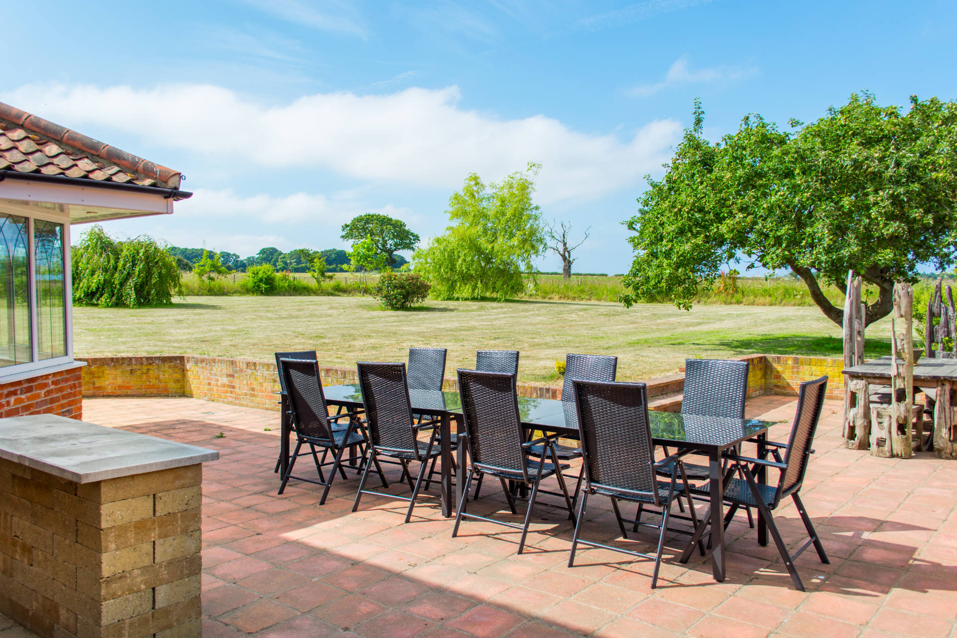 Outside patio and dining area with garden and countryside views.