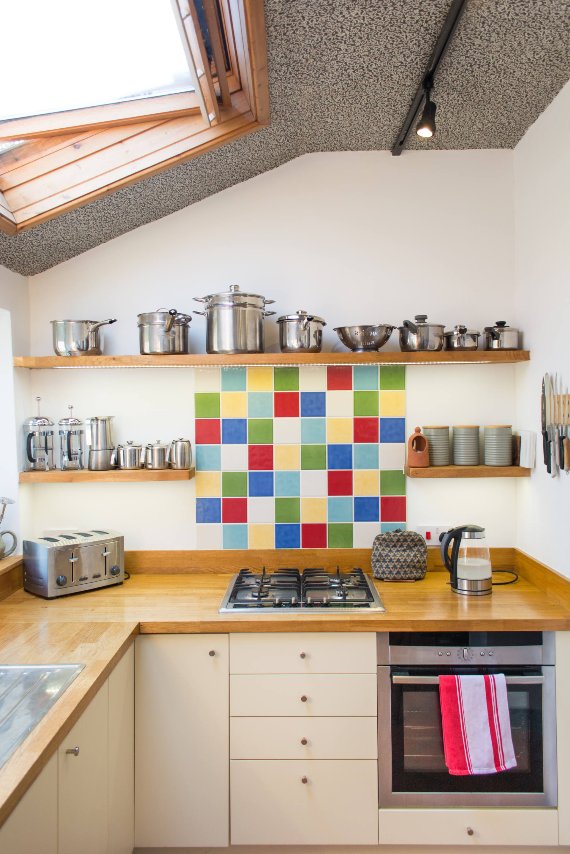 Holiday home kitchen with colourful tiles, and kitchen utensils.