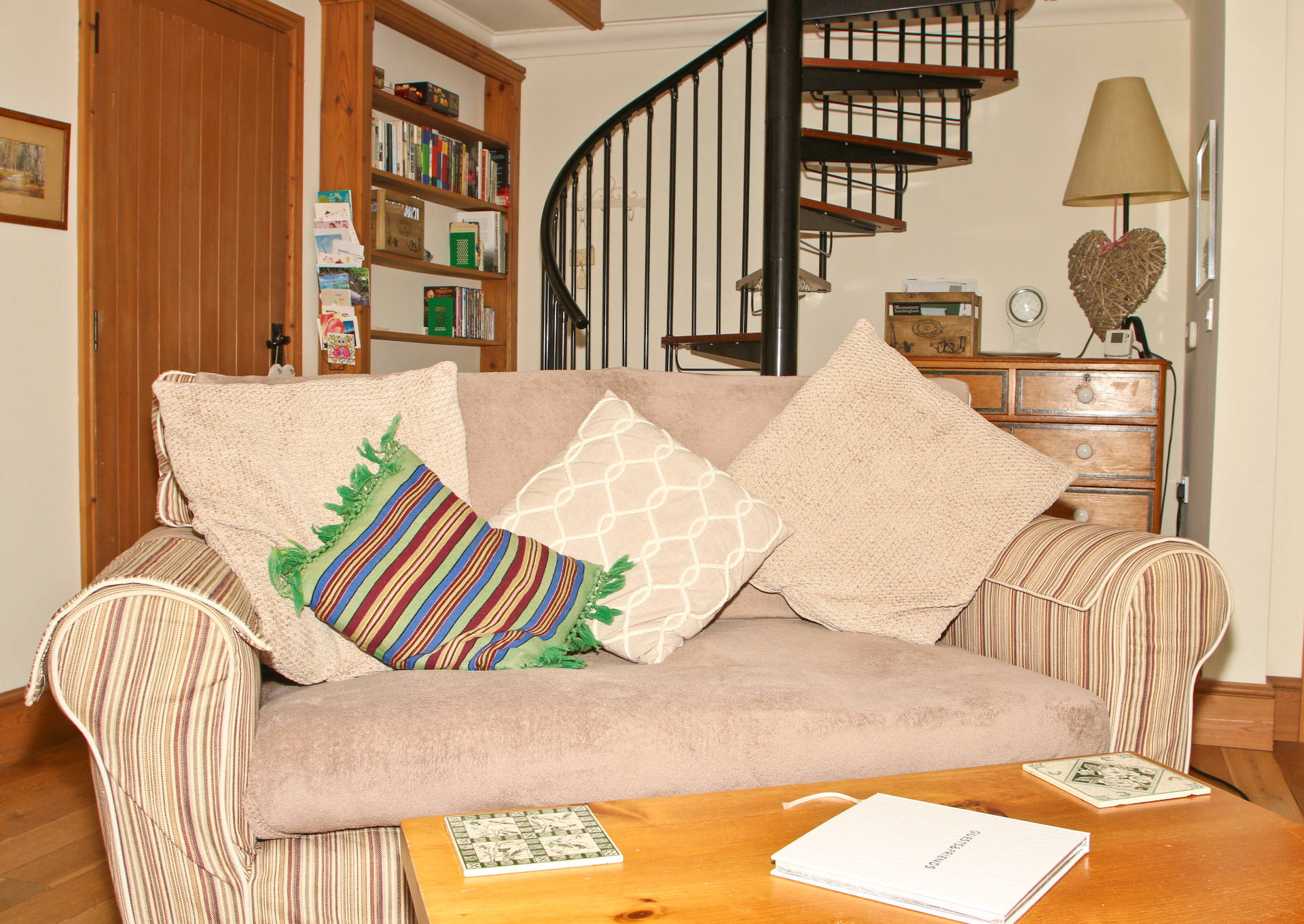 Holiday home living room with sofa and spiral staircase.