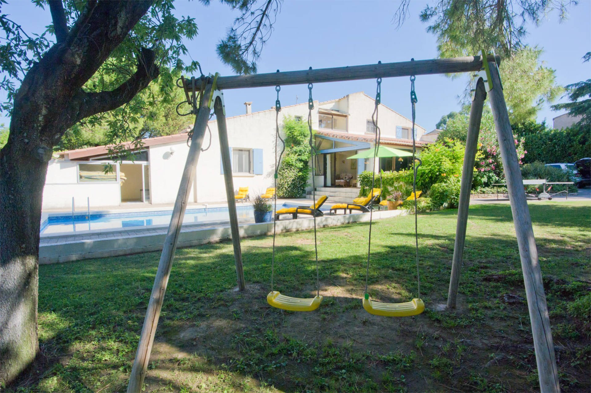 Outside swing set by the swimming pool.