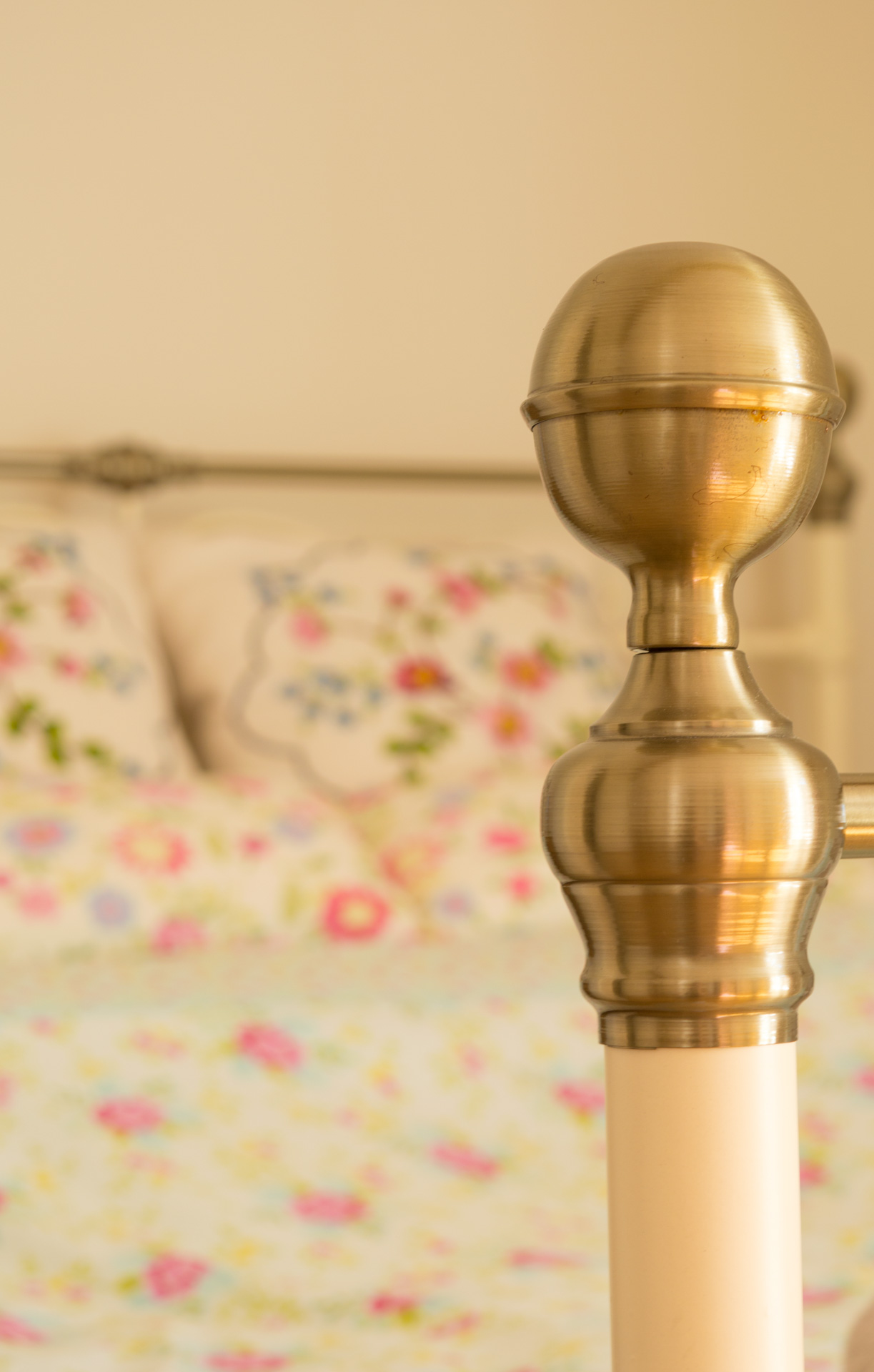 Close up shot of gold ended bed post.