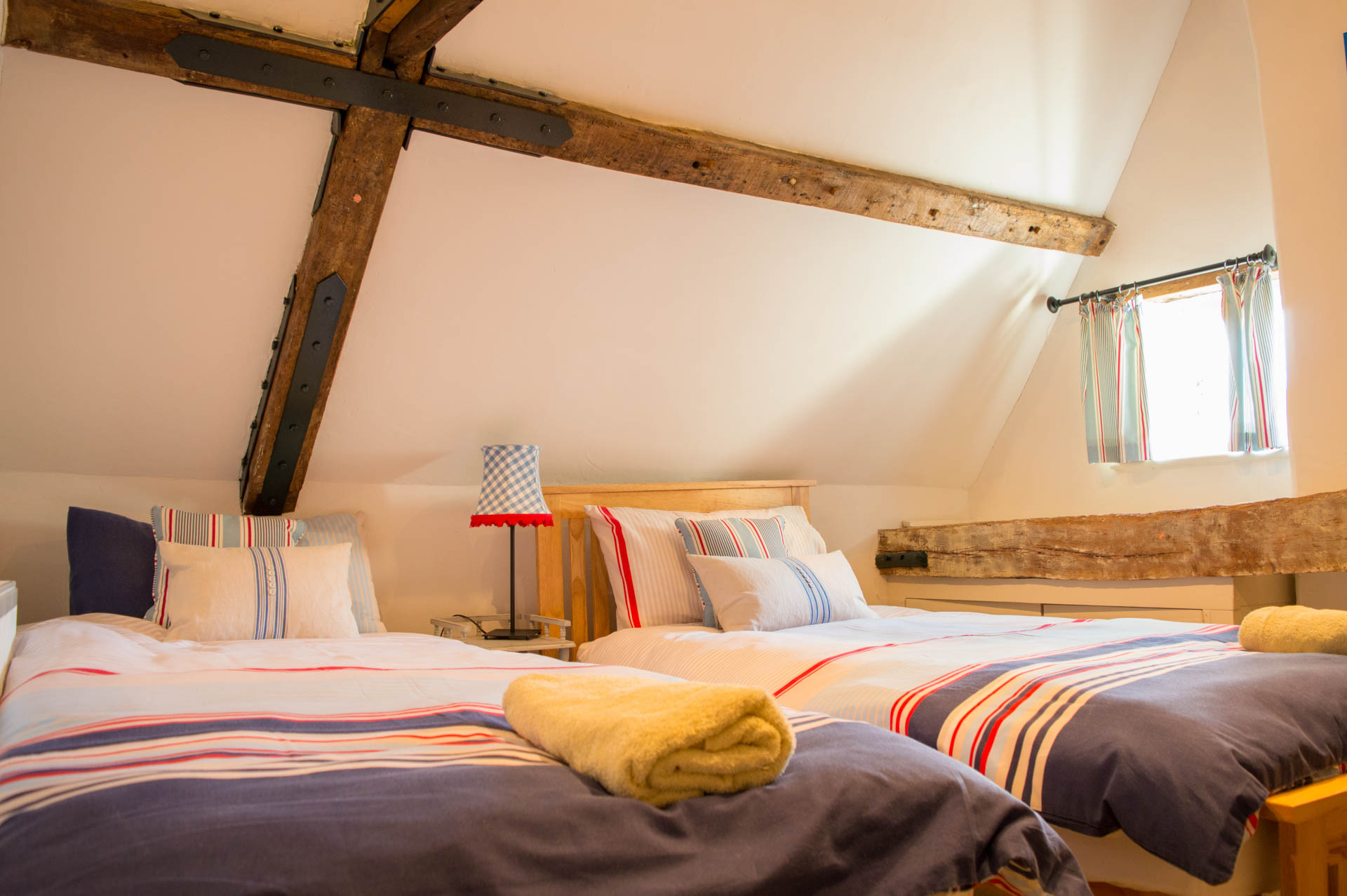 Twin bedroom with wooden ceiling beams.