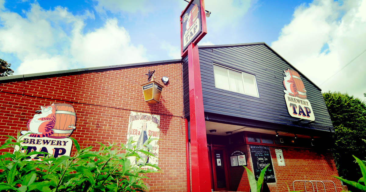 Image of the outside of The Fat Cat Brewery Tap taken from a low angle on a sunny day.