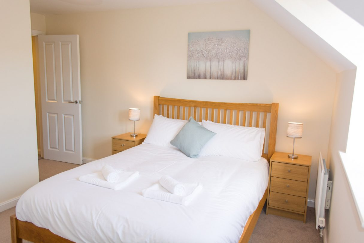King-sized bedroom with bedside tables either side of the wooden framed bed.