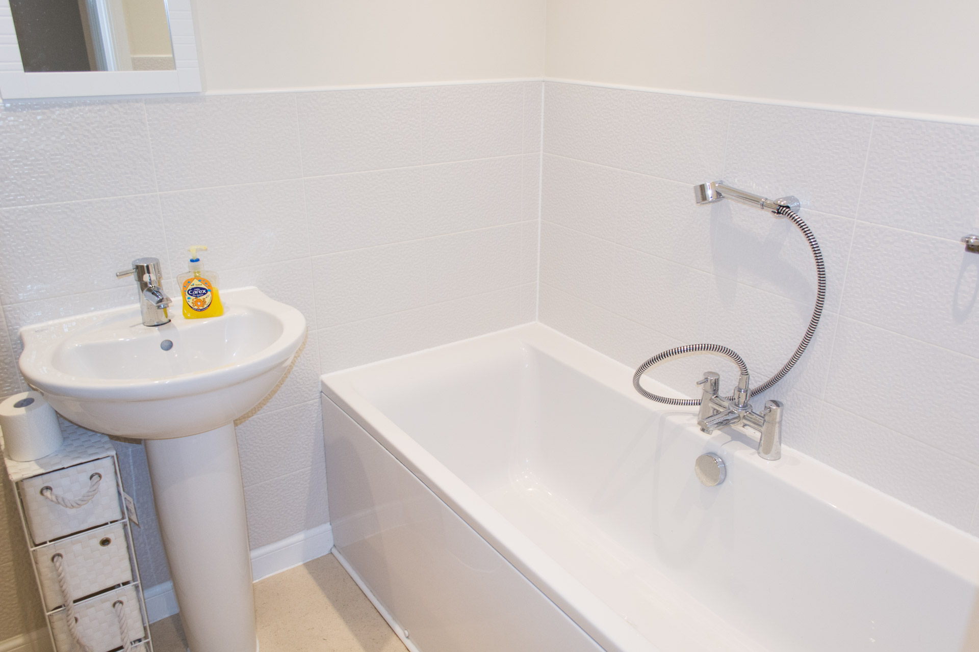 Family bathroom with bath tub and sink.