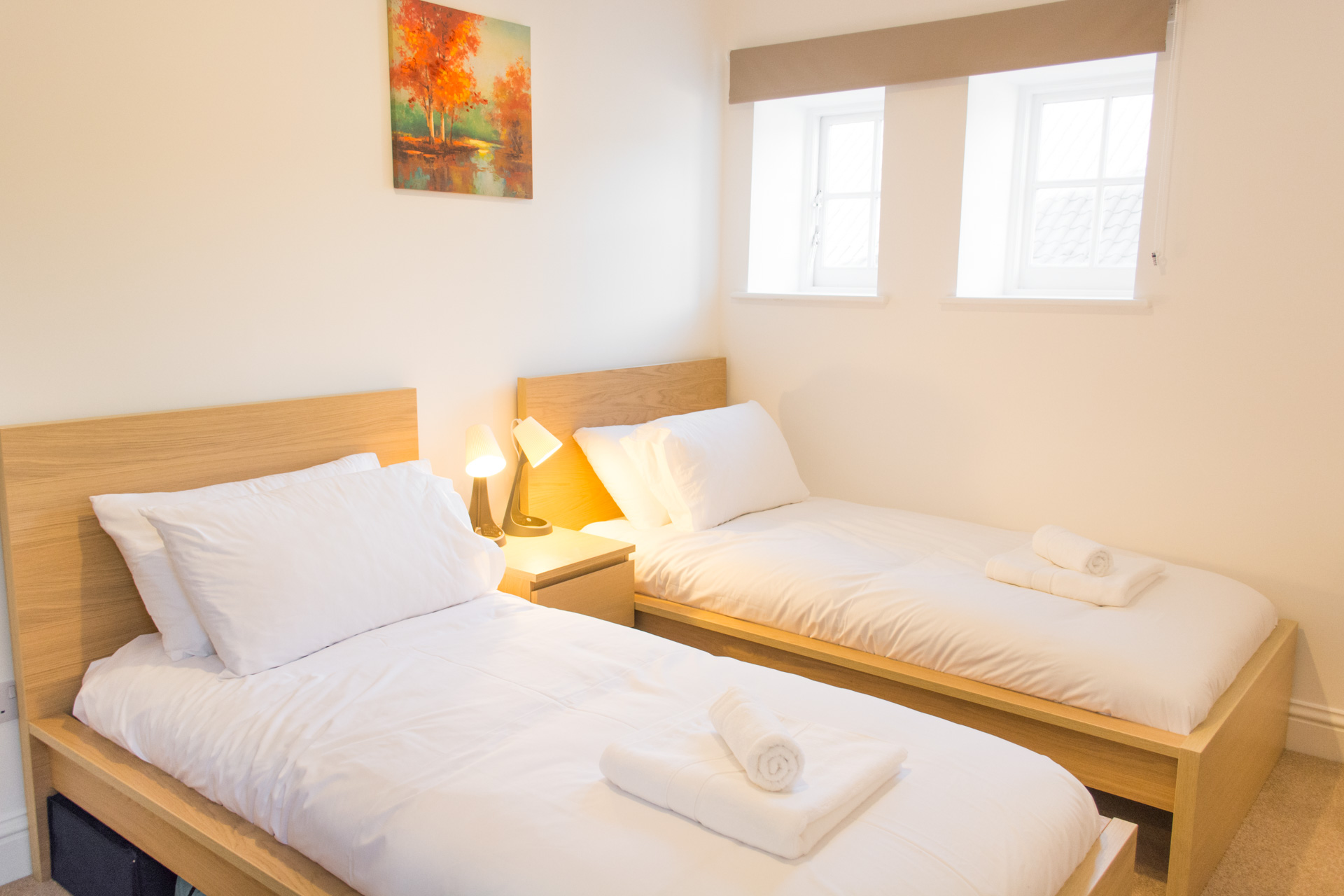Twin bedroom, with white linen and bedside lamps.