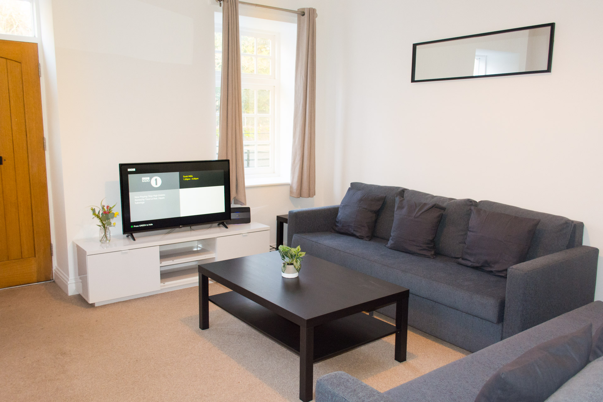 Family living area, with coffee table and flat screen television.