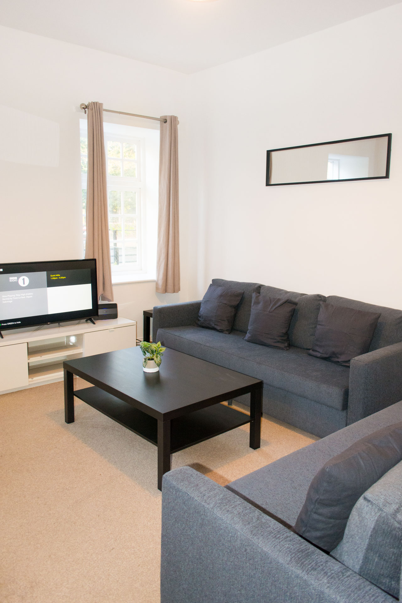 Wide angle shot of grey sofas, black coffee table and living area.