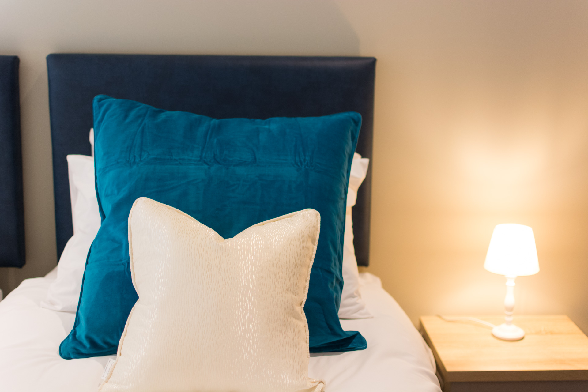 Close up photo of large blue and small white pillows in a twin bedroom.