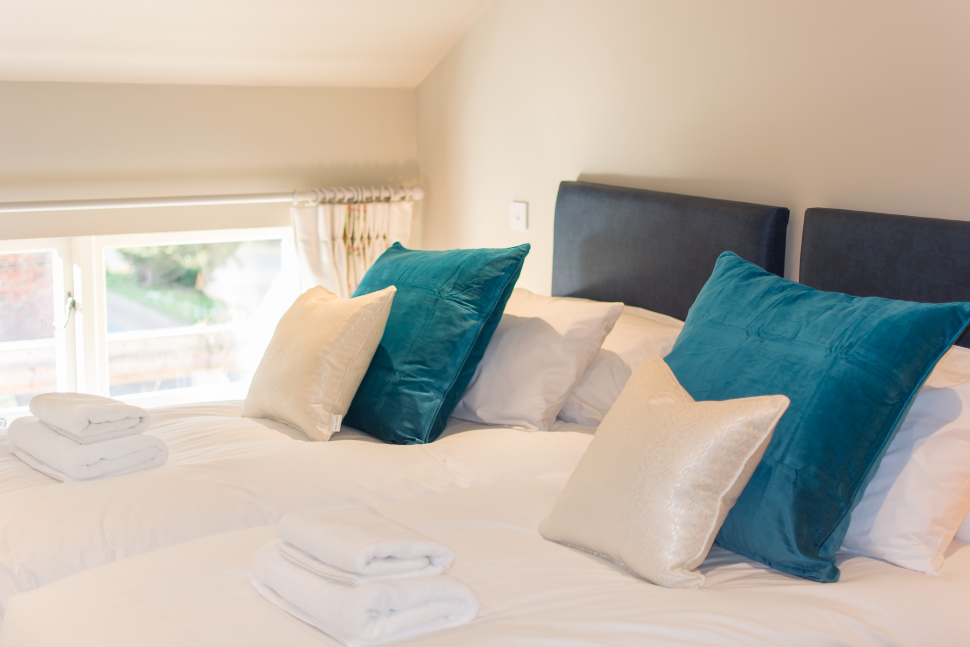Upstairs twin room with white linen and large blue pillows.