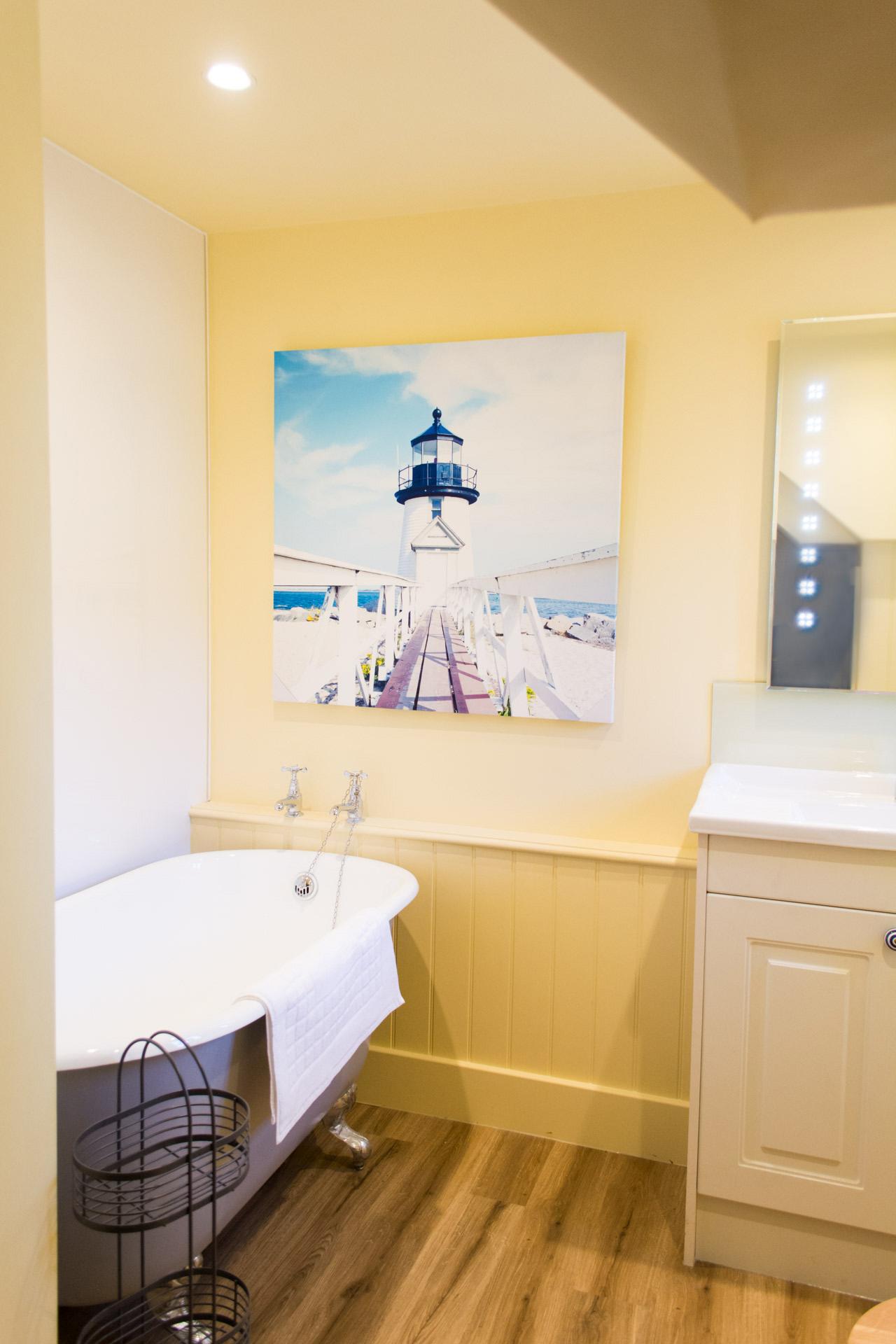 Bathroom photo showing yellow walls and bath tub.