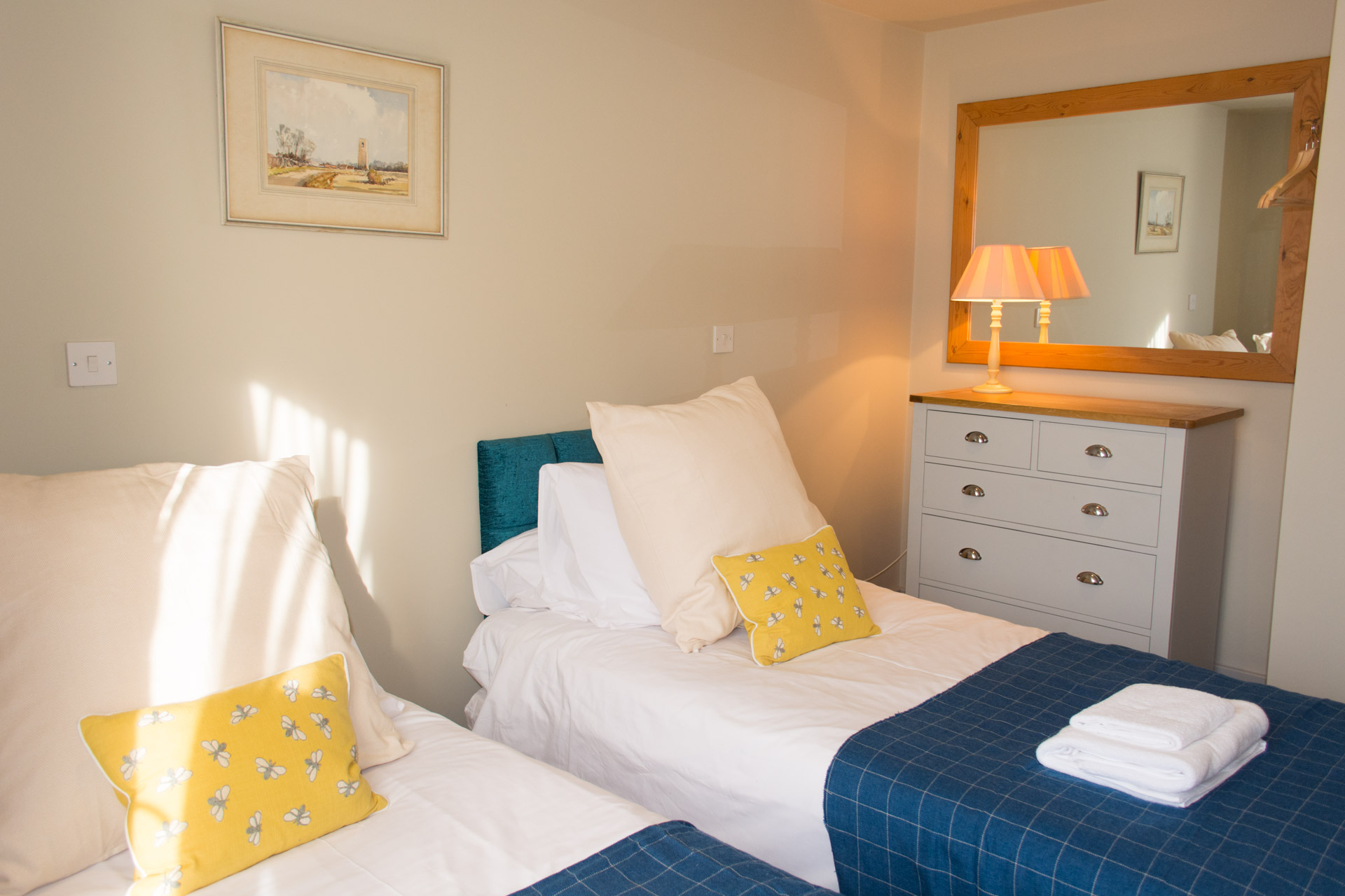 Holiday home twin room with blue blankets and white linen.