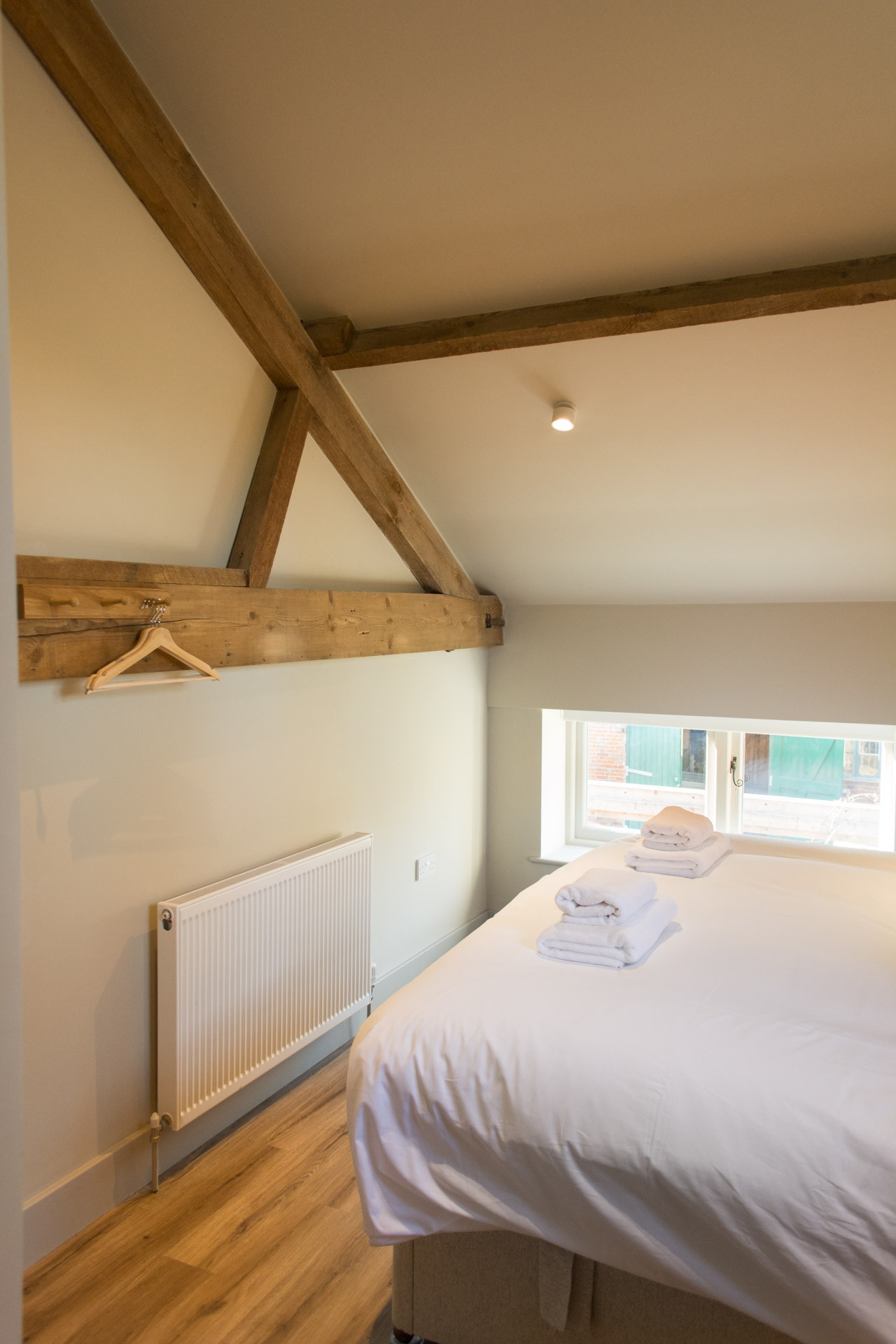 Super-king bedroom showing wooden beams on the walls and ceiling.