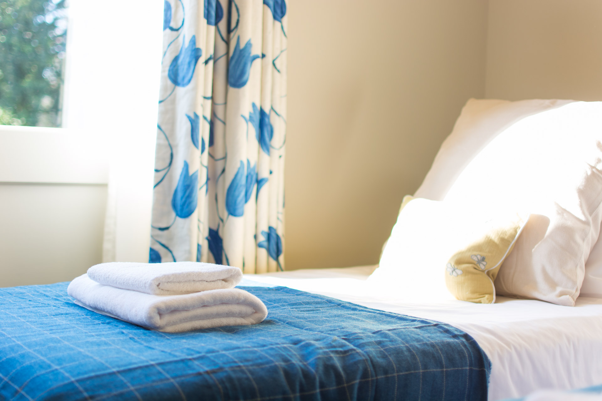 Close up photo of white towel on twin room bed.