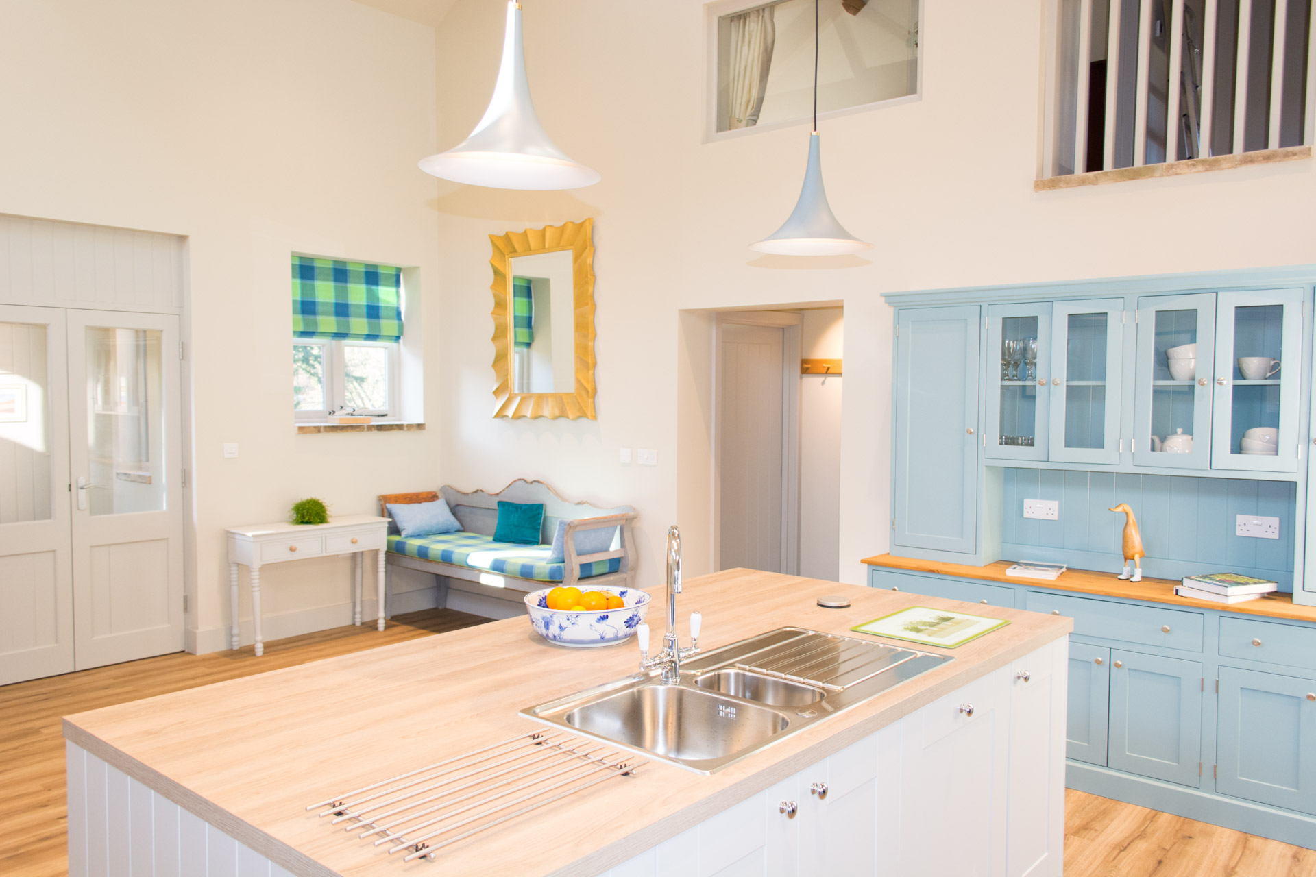 Renovated kitchen showing the kitchen island and sink angled towards the entrance to Boathouse Barn.