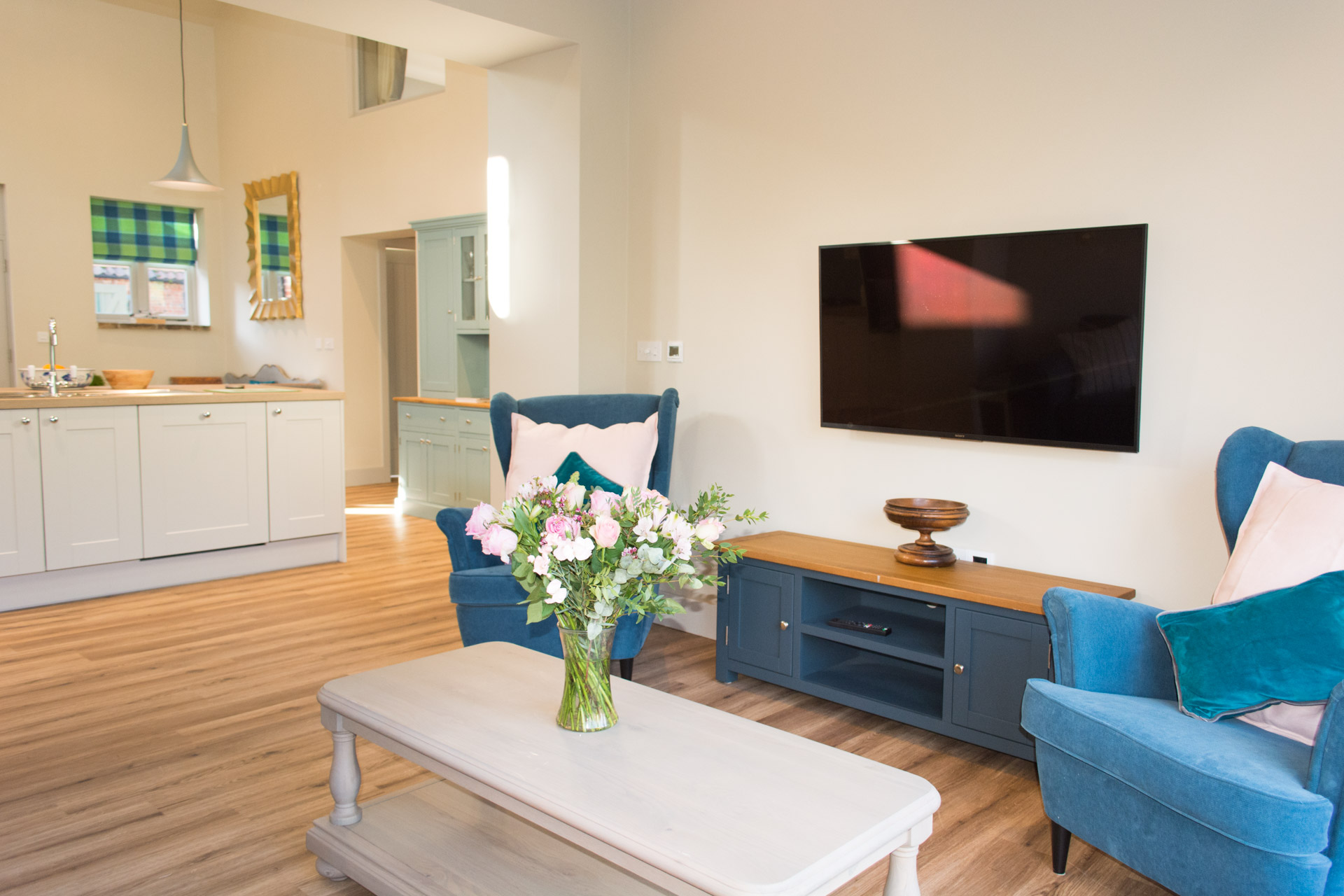 Interior holiday cottage living area showing a TV and blue armchairs.