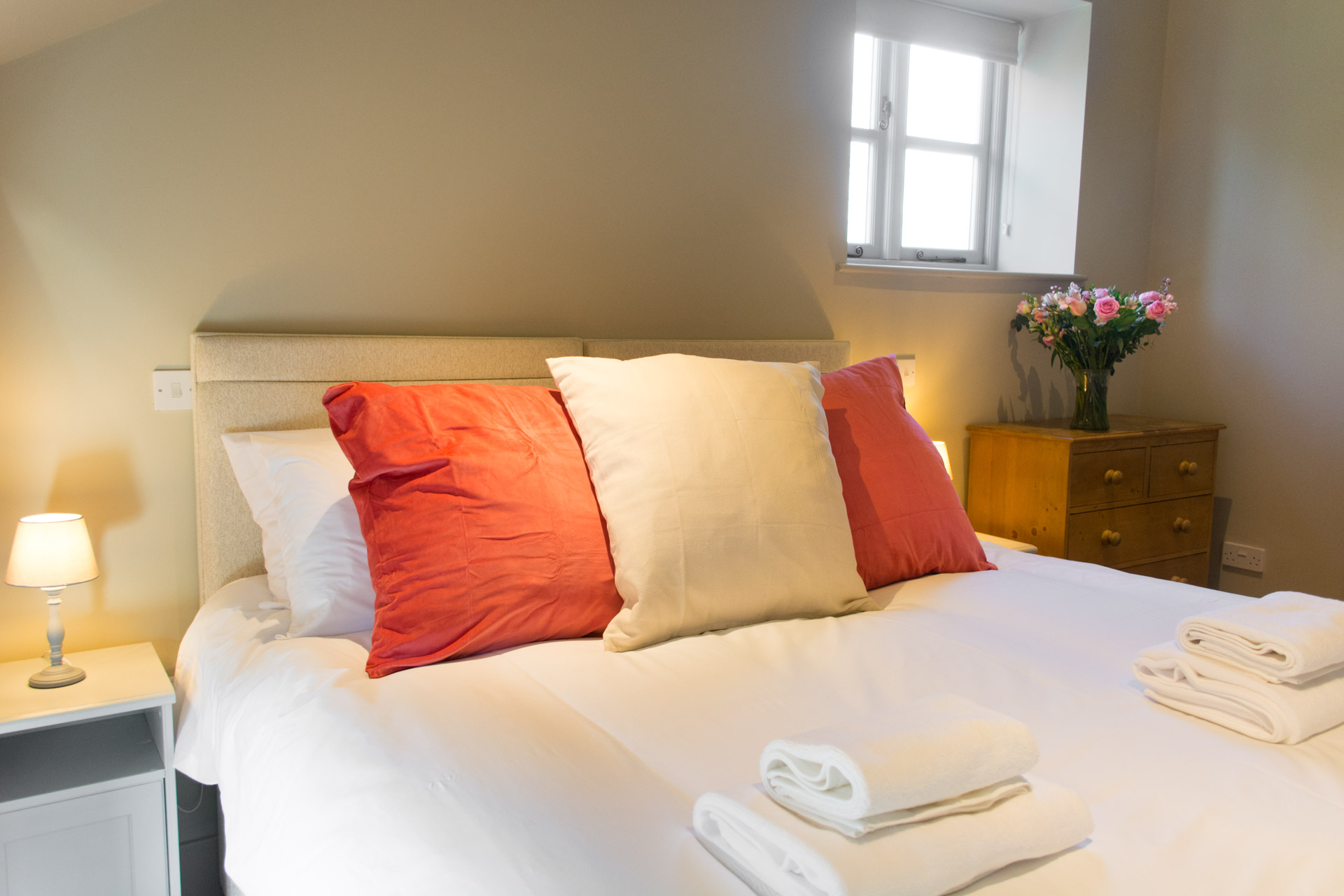 Close up of large red and white pillows with towels laid on the bed.
