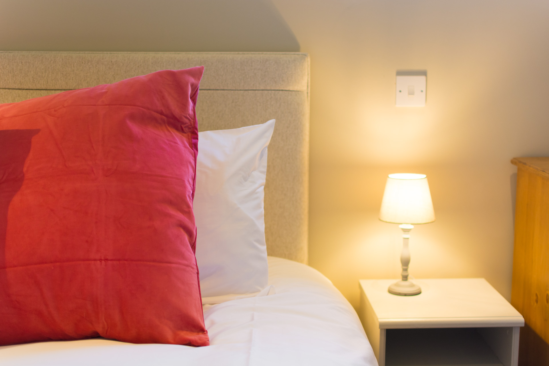 Close up photo of Super-king bedroom pillows and night light.