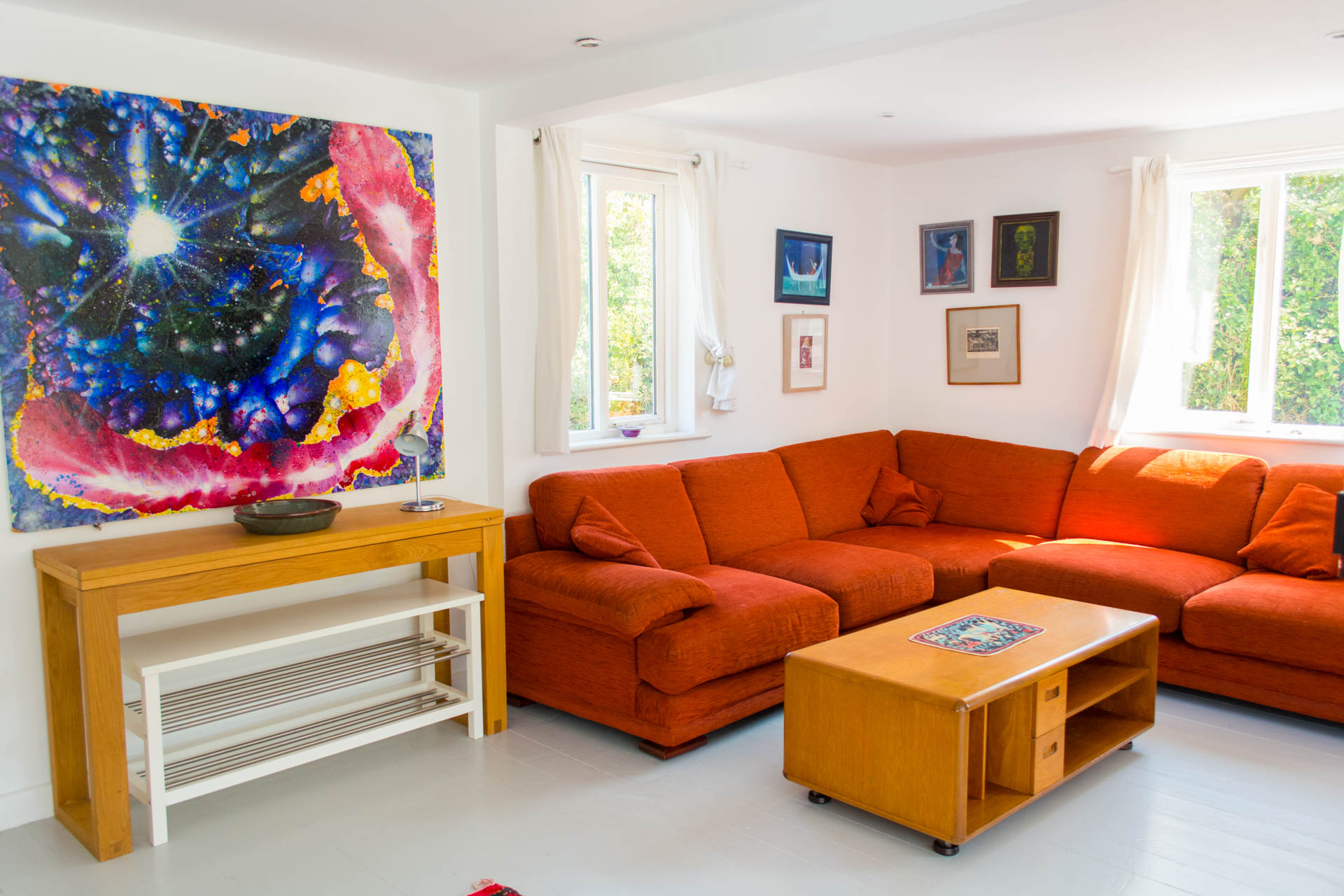 Photo of spacious living area and coffee table with colourful art work on the walls.
