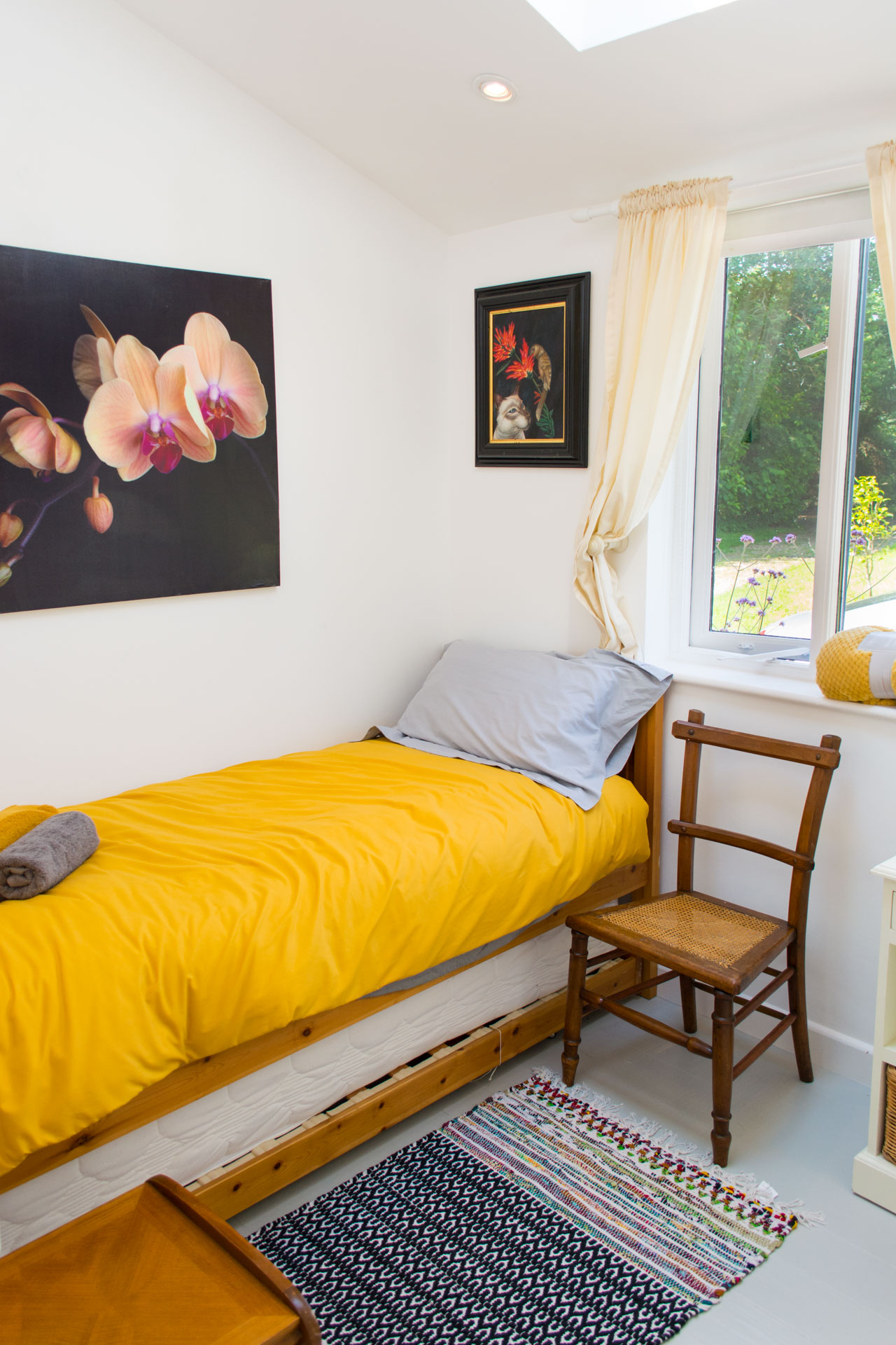 Single bedroom showing a bed with a yellow duvet and grey pillow.