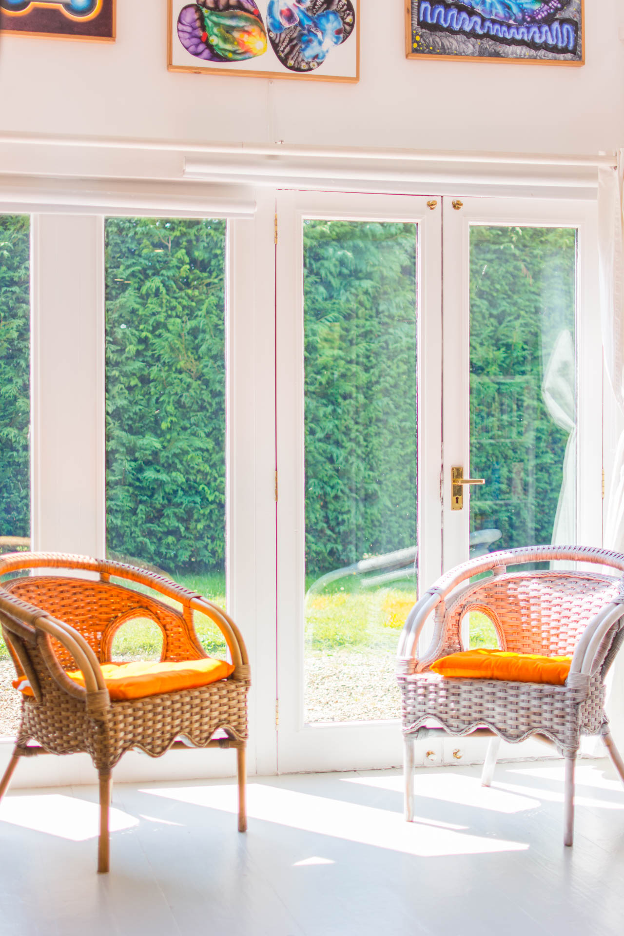 Photo of two chairs in front of glass doors leading out to the garden.