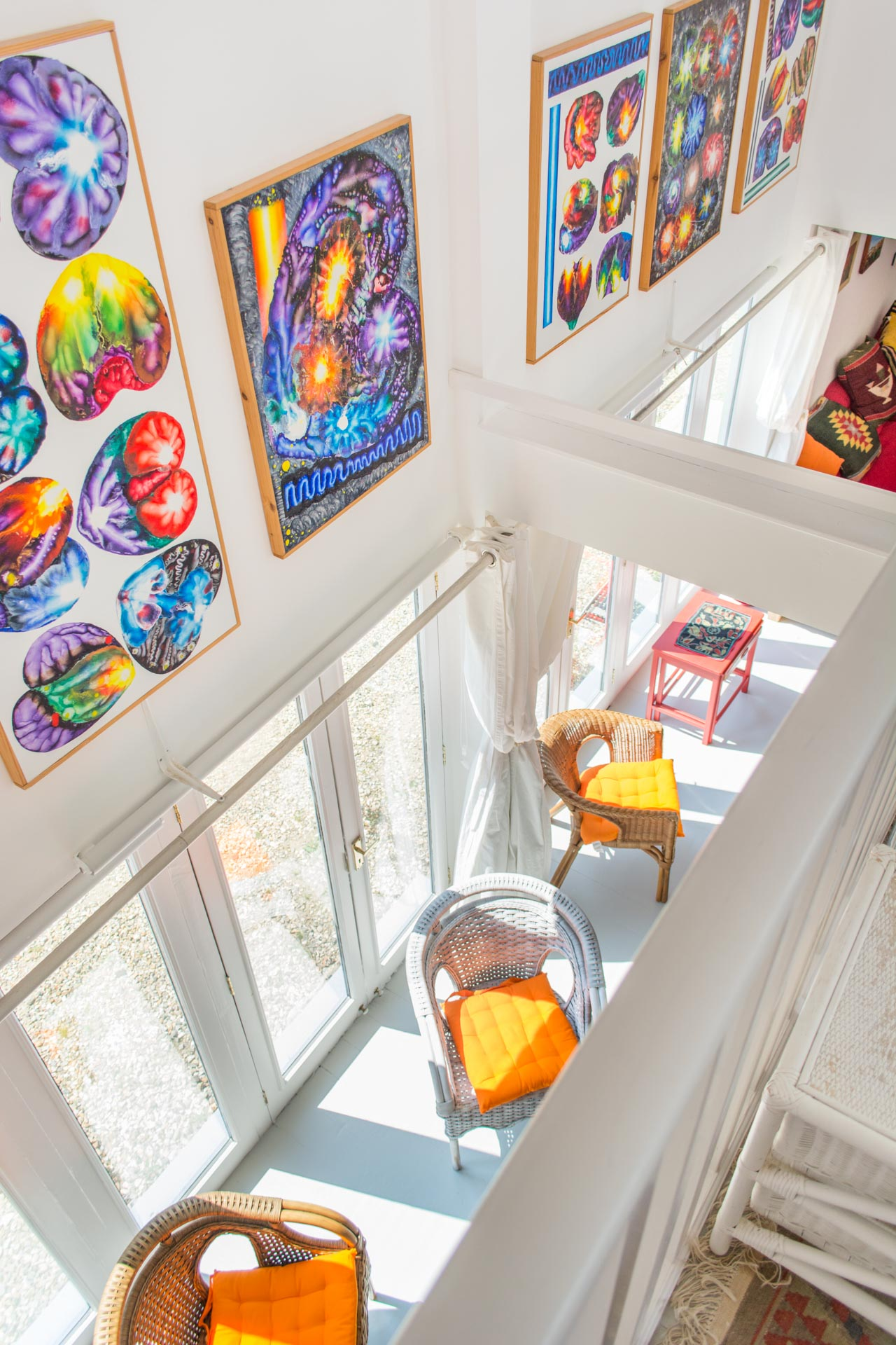 Photo taken from the mezzanine level showing colourful artwork on the walls and chairs on the ground floor.