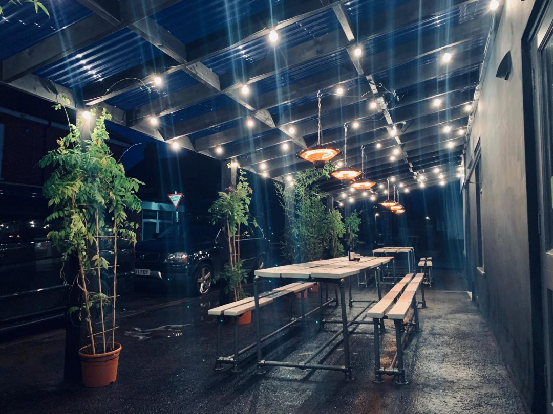 Woolf and Social new outside area with ceiling lighting and a wooden bench.
