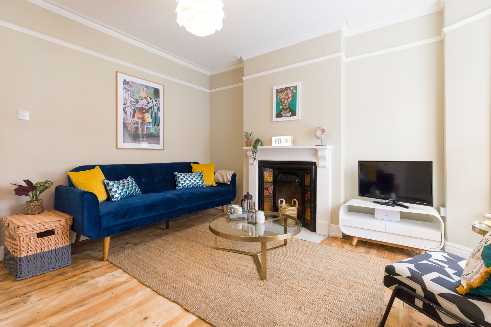 Living room with blue sofa and yellow pillows.
