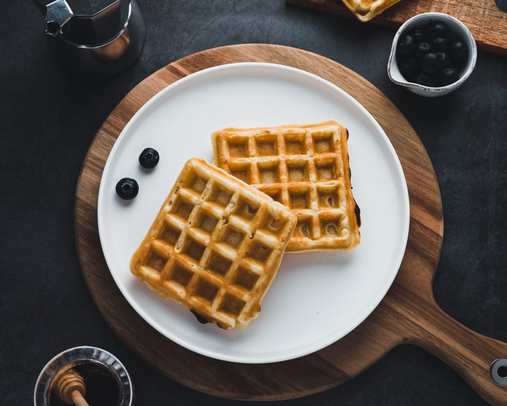 A plate of two waffles on a wood chopping board with berries and a side of syrup.