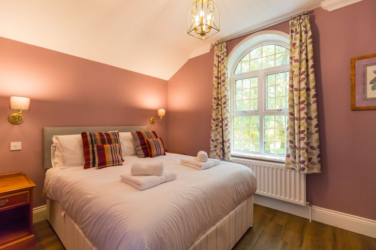 Redwings holiday apartments bedroom with white linen and pink walls.
