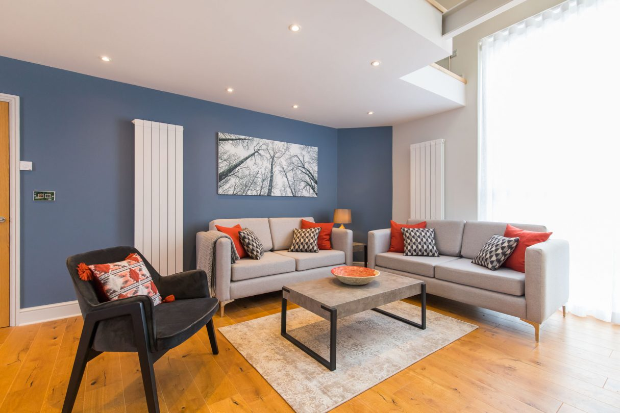 Holt holiday cottage living room with hardwood floors, grey sofas and red cushions..