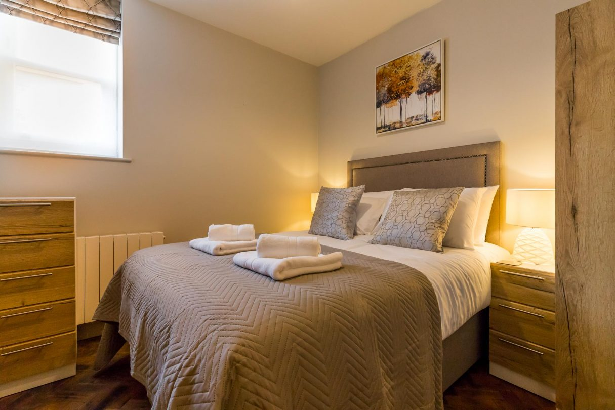 Double bedroom with bedside lamps and towels.